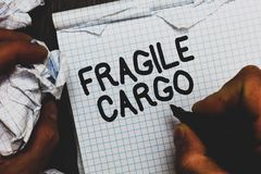 Handwriting text Fragile Cargo. Concept meaning Breakable Handle with Care Bubble Wrap Glass Hazardous Goods Man holding marker no. Tebook crumpled papers ripped stock image