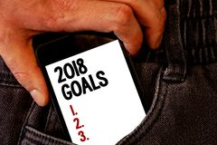 Handwriting text 2018 Goals 1. 2. 3.. Concept meaning Resolution Organize Beginnings Future Plans Brown jeans back pocket hand pus. Hing mobile phone with black stock image