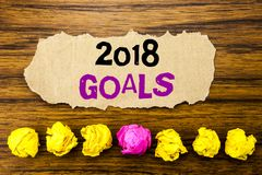 Handwriting text 2018 Goals. Concept for New Yer resolutions Written on sticky note paper reminder, wooden background with stick stock photography