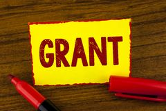 Handwriting text Grant. Concept meaning Money given by an organization or government for a purpose Scholarship written on Yellow S. Handwriting text Grant stock photography