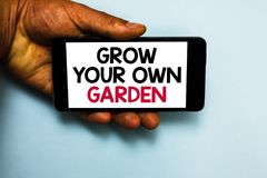 Handwriting text Grow Your Own Garden. Concept meaning Organic Gardening collect personal vegetables fruits Human hand hold mobile. Phone with some black and royalty free stock image