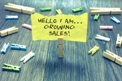 Handwriting text Hello I Am... Growing Sales. Concept meaning Making more money Selling larger quantities Paperclip hold written t. Orn page many clips laid on stock image