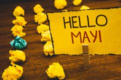 Handwriting text Hello May Motivational Call. Concept meaning Starting a new month April is over SpringClothespin holding Yellow p stock photos