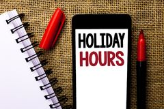 Handwriting text Holiday Hours. Concept meaning Celebration Time Seasonal Midnight Sales Extra-Time Opening written on Mobile Phon. Handwriting text Holiday royalty free stock images