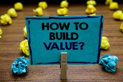Handwriting text How To Build Value question. Concept meaning Ways for developing growing building a business Blurry wooden deck y. Ellow and blue lob on ground stock image