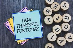 Handwriting text I Am Thankful For Today. Concept meaning Grateful about living one more day Philosophy Black wooden deck written. Sticky note beside some round royalty free stock image