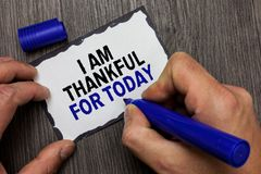 Handwriting text I Am Thankful For Today. Concept meaning Grateful about living one more day Philosophy Gray wooden deck hand hold. Black marker written black stock photos