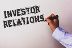 Handwriting text Investor Relations. Concept meaning Finance Investment Relationship Negotiate Shareholder Advisors hand holding b. Lack marker whiteboard stock photography