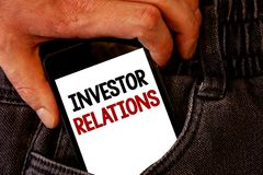 Handwriting text Investor Relations. Concept meaning Finance Investment Relationship Negotiate Shareholder Brown jeans back pocket. Hand pushing mobile phone stock photo