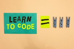 Handwriting text Learn To Code. Concept meaning Learn to write Software Be a Computer Programmer Coder Turquoise paper reminder eq. Ual sign several clothespins stock image