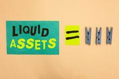 Handwriting text Liquid Assets. Concept meaning Cash and Bank Balances Market Liquidity Deferred Stock Turquoise paper reminder eq. Ual sign several clothespins royalty free stock photo
