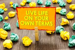 Handwriting text Live Life On Your Own Terms. Concept meaning Give yourself guidelines for a good living Paperclip hold written ye. Llow page colorful paper lobs stock photo