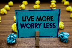 Handwriting text Live More Worry Less. Concept meaning Have a good attitude motivation be careless enjoy life Blurry wooden deck y royalty free stock photography