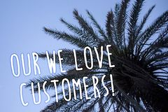 Handwriting text We Love Our Customers Call. Concept meaning Client deserves good service satisfaction respect Tall palm tree blue. Sky ideas messages thoughts Royalty Free Stock Image