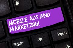 Handwriting text Mobile Ads And Marketing. Concept meaning Online advertising social media digital promotions Keyboard. Key Intention to create computer message stock photo