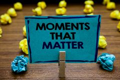 Handwriting text Moments That Matter. Concept meaning Meaningful positive happy memorable important times Blurry wooden deck yello. W and blue lob on ground stock images