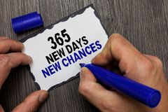 Handwriting text 365 New Days New Chances. Concept meaning Starting another year Calendar Opportunities Gray wooden deck hand hold. Black marker written black royalty free stock photography