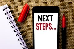 Handwriting text Next Steps.... Concept meaning Following Moves. Strategy Plan Give Directions Guideline written Mobile Phone the jute background Marker and Stock Photography