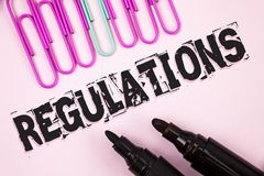 Handwriting text Regulations. Concept meaning Rules Laws Corporate Standards Policies Security Statements written on Plain Pink ba. Handwriting text Regulations Stock Photography