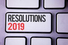 Handwriting text Resolutions 2019. Concept meaning Positive reinforcement personal improvent corporate goals written on white keyb. Handwriting text Resolutions Stock Photo
