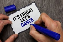 Handwriting text It s is Friday Let s is Dance. Concept meaning Celebrate starting the weekend Go party Disco Music Gray wooden de. Ck hand hold black marker royalty free stock photography