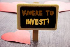 Handwriting text showing Where To Invest Question. Business photo showcasing Financial Income Investing Plan Advice Wealth written. Blackboard the wooden Royalty Free Stock Photo