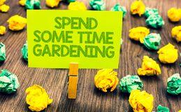 Handwriting text Spend Some Time Gardening. Concept meaning Relax planting flowers fruits vegetables Natural Paperclip retain writ. Ten words yellow paper paper stock photography