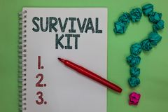 Handwriting text Survival Kit. Concept meaning Emergency Equipment Collection of items to help someone Notebook marker crumpled pa royalty free stock photo