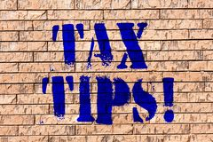 Handwriting text Tax Tips. Concept meaning Help Ideas for taxation Increasing Earnings Reduction on expenses Brick Wall. Handwriting text Tax Tips. Conceptual royalty free stock photography