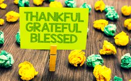 Handwriting text Thankful Grateful Blessed. Concept meaning Appreciation gratitude good mood attitude Paperclip retain. Written words yellow paper paper lobs stock photos