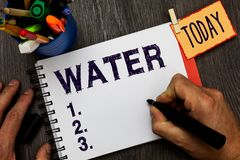 Handwriting text Water. Concept meaning colourless transparent odourless liquid which forms seas rivers Man holding. Marker notebook clothespin hold reminder stock photos