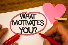 Handwriting text What Motivates You Question. Concept meaning Passion Drive Incentive Dream Aspiration Human hand retain red pen c. Ircled black words paper hook stock photography