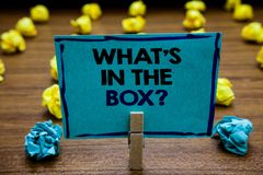 Handwriting text What s is In The Box question. Concept meaning Curiosity Opening a gift Surprise package Blurry wooden deck yello. W and blue lob on ground stock photography