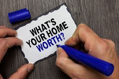 Handwriting text What s is Your Home Worth question. Concept meaning Value of a house Property Cost Price Rate Gray wooden deck ha. Nd hold black marker written stock photos