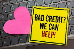 Handwriting text writing Bad Credit question We Can Help. Concept meaning Borrower with high risk Debts Financial Written on black. Bordered yellow page touched stock photo