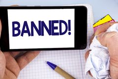 Handwriting text writing Banned Motivational Call. Concept meaning Ban on use of steroids, No excuse for building Muscles. written. Mobile Phone holding by man stock photography