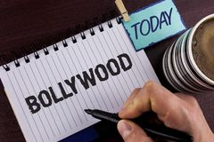 Handwriting text writing Bollywood. Concept meaning Indian cinema a source of entertainment written by Man on Notepad holding Mark. Handwriting text writing royalty free stock photography