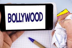 Handwriting text writing Bollywood. Concept meaning Indian cinema a source of entertainment written on Mobile Phone Screen holding. Handwriting text writing Royalty Free Stock Photo