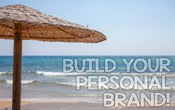 Handwriting text writing Build Your Personal Brand Motivational Call. Concept meaning creating successful company Blue beach water. Thatched Straw Umbrellas royalty free stock image