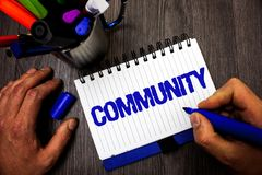 Handwriting text writing Community. Concept meaning Neighborhood Association State Affiliation Alliance Unity Group Man hold holdi. Ng marker notebook ideas Stock Photo