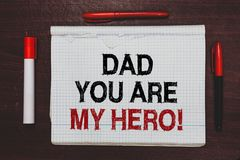 Handwriting text writing Dad You Are My Hero. Concept meaning Admiration for your father love feelings compliment Written black, r. Ed words notepad on brown royalty free stock image