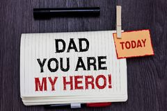 Handwriting text writing Dad You Are My Hero. Concept meaning Admiration for your father love feelings compliment Written paper on. Wooden desk paper clip grip royalty free stock image