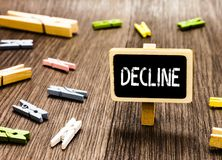 Handwriting text writing Decline. Concept meaning Become smaller fewer less Decrease Politely refuse reject say no. Blackboard standing several clothespins stock image