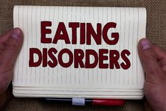 Handwriting text writing Eating Disorders. Concept meaning any of a range of psychological abnormal food habits Man. Hands holding notebook open page jute stock photo