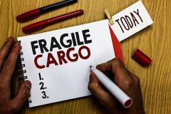 Handwriting text writing Fragile Cargo. Concept meaning Breakable Handle with Care Bubble Wrap Glass Hazardous Goods Man holding m. Arker notebook clothespin royalty free stock photo
