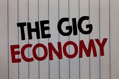 Handwriting text writing The Gig Economy. Concept meaning Market of Short-term contracts freelance work temporary white vertical p. Aper written three words with stock photo