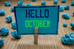 Handwriting text writing Hello October. Concept meaning Last Quarter Tenth Month 30days Season Greeting Clothespin holding blue pa royalty free stock photos