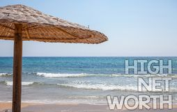 Handwriting text writing High Net Worth. Concept meaning having high-value Something expensive A-class company Blue beach water Th. Atched Straw Umbrellas stock photo