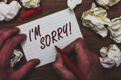 Handwriting text writing I am Sorry. Concept meaning To ask for forgiveness to someone you unintensionaly hurt Man holding marker. Notebook page crumpled papers stock image