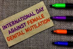Handwriting text writing International Day Against Female Genital Mutilation. Concept meaning awareness day February Paperboard co. Mputer mouse jute background Royalty Free Stock Images
